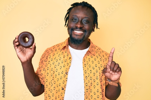 Young african american man with braids holding donut surprised with an idea or question pointing finger with happy face, number one