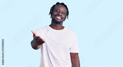 Young african american man with braids wearing casual white tshirt smiling cheerful offering palm hand giving assistance and acceptance.