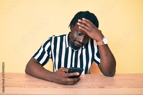Young african american man with braids using smartphone sitting on the table stressed and frustrated with hand on head, surprised and angry face