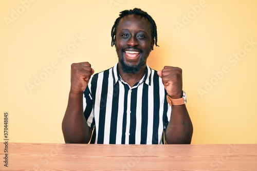Young african american man with braids wearing casual clothes sitting on the table screaming proud, celebrating victory and success very excited with raised arms
