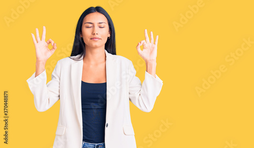 Young beautiful latin girl wearing business clothes relax and smiling with eyes closed doing meditation gesture with fingers. yoga concept.