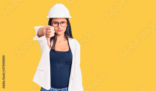 Young beautiful latin girl wearing architect hardhat and glasses looking unhappy and angry showing rejection and negative with thumbs down gesture. bad expression.