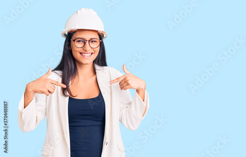 Young beautiful latin girl wearing architect hardhat and glasses looking confident with smile on face, pointing oneself with fingers proud and happy.