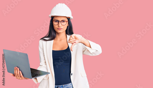 Young beautiful latin girl wearing architect hardhat holding laptop with angry face, negative sign showing dislike with thumbs down, rejection concept