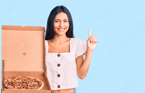 Young beautiful latin girl holding delivery pizza box surprised with an idea or question pointing finger with happy face, number one