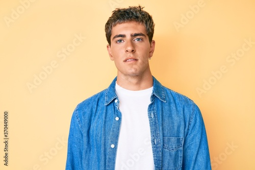Young handsome man wearing casual clothes relaxed with serious expression on face. simple and natural looking at the camera.