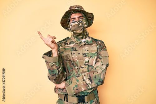 Young handsome man wearing camouflage army uniform and balaclava smiling happy pointing with hand and finger to the side