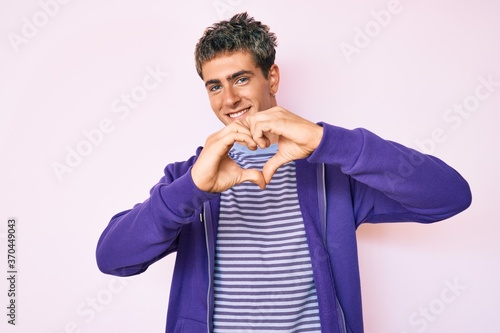 Young handsome man wearing casual purple sweatshirt smiling in love showing heart symbol and shape with hands. romantic concept.