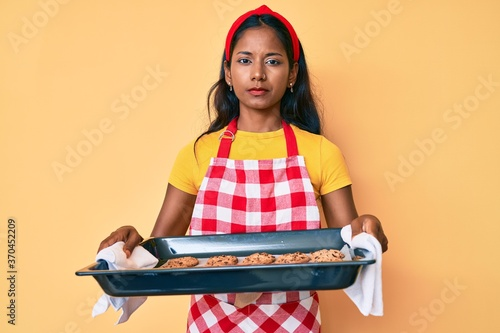 Photo Young indian girl wearing baker uniform holding homemade cookies relaxed with serious expression on face