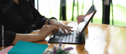 Female hands typing on tablet keyboard on worktable in glass wall office room Canvas Print