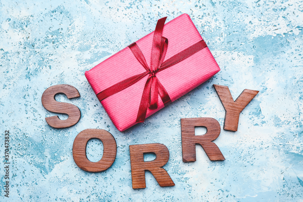 Fototapeta Gift with word SORRY on color background