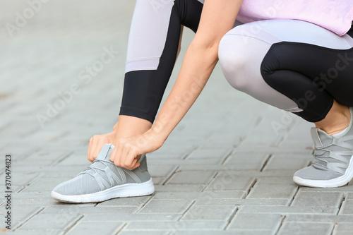 Obraz Sporty young woman tying shoelaces outdoors - fototapety do salonu