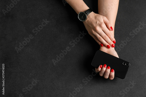 Obraz Hands with beautiful manicure and mobile phone on dark background - fototapety do salonu