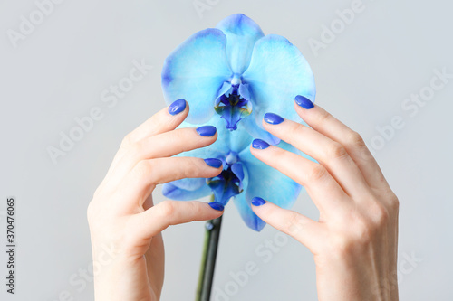 Obraz Hands with beautiful manicure and flowers on light background - fototapety do salonu