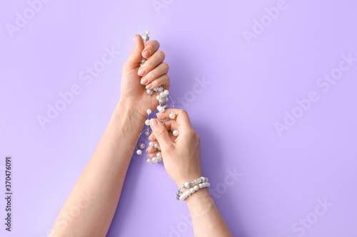 Obraz Hands with beautiful manicure holding necklace on color background - fototapety do salonu