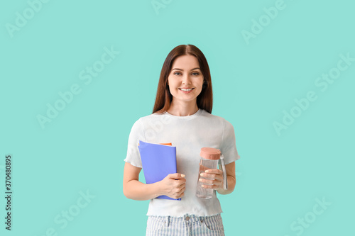 Obraz Young woman with bottle of water on color background - fototapety do salonu