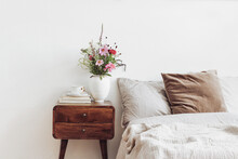 Cup Of Coffee And Books On Retro Wooden Bedside Table. Rustic White Ceramic Vase With Bouquet Of Pink Cocmos And Zinnia Flowers. Beige Linen And Velvet Pillows In Bed. Scandinavian Interior, Bedroom.