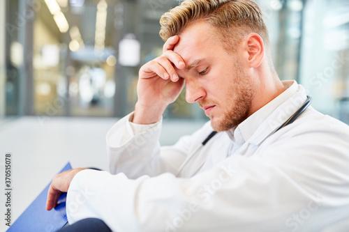 Foto Junger Arzt sitzt erschöpft im Krankenhaus