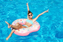 Cute Smiling Little Girl In Swimming Pool With Rubber Ring