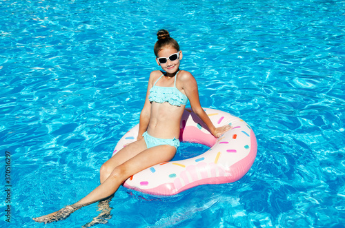 Obraz Cute smiling little girl in swimming pool with rubber ring - fototapety do salonu