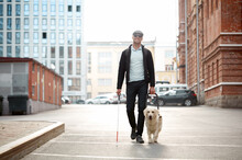 Blind Man With Cane And Guide Dog Walking On Pavement In Town, Adorable Golden Retriever Help His Disabled Owner, Dog Is Best Friend