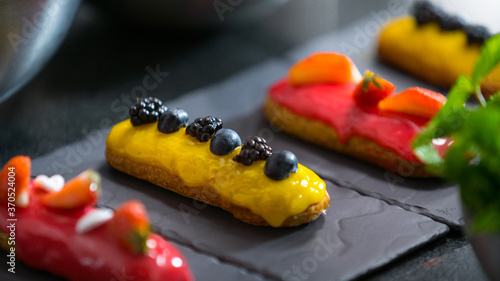 Fotografie, Obraz Decorating pink glaze eclair with strawberry, mint