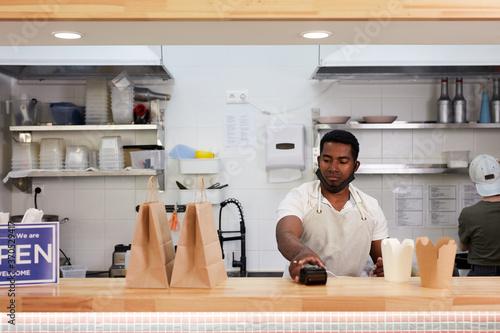 Fotografia, Obraz handsome black salesman preparing takeaway orders in cafe, wait for clients, ser