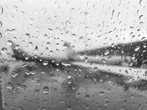 Fotografie, Obraz The blurred wing of the plane is visible through a drop of rain on the window of