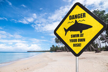 A Shark Warning Sign At The Beach. Shark Season Or Shark Infested Waters. A Stern Warning To Bathers That They Are At Great Risk. Tropical Beach Setting.