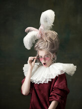 Stylish Eyewear. Young Woman As Marie Antoinette Isolated On Dark Green Background. Retro Style, Comparison Of Eras Concept. Beautiful Female Model Like Classic Historical Character, Old-fashioned.