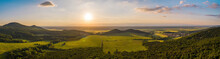 Summer Nature Scenery At Sunset With Green Forests And Meadow And Blue Sky. Panoramic Aerial View On Hills With Orange Sun Shining Above Horizon With Copy Space.
