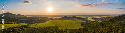 Obraz na plátne Summer nature scenery at sunset with green forests and meadow and blue sky