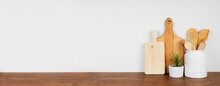 Kitchenware And Utensils On A Wooden Shelf Or Counter. Banner With A White Wall Background And Copy Space. Kitchen Cooking Decor.