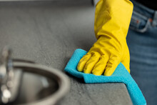 Woman's Hands In Yellow Gloves Cleaning Counter Top In Kitchen