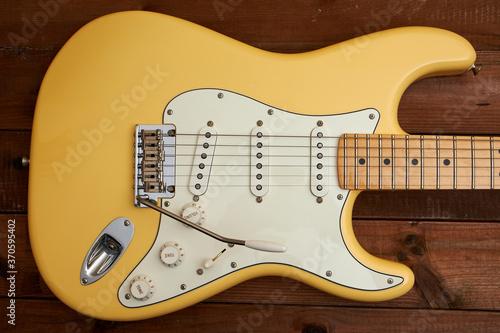 Obraz na płótnie Butter colored Strat guitar on dark table