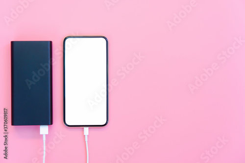 Smartphone charging with power bank on pink background Wallpaper Mural