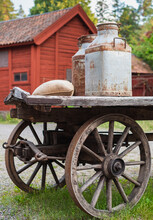 Old Wooden Wagon With Grain Sack And Metal Milk Churns