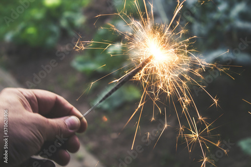 Fotografie, Obraz Festive sparkles of a burning Sparkler in a man's hand