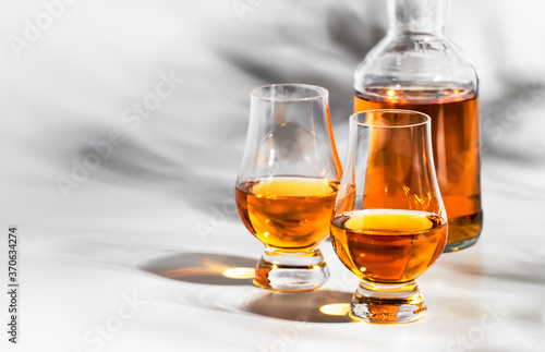 Photographie Scotch Whiskey without ice in glasses and bottle, white background with hard lig