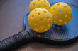 Two pickleballs. Pickleball is a popular American sport played with paddles and whiffleballs on a court 1/4 size of a tennis court.