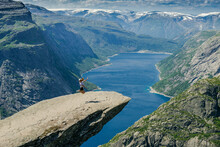 Girl Sitting On The Edge Of A Rocky Cliff. Extreme Tourism. Trolltunga. Troll Language In Norway. Rocky Ledge Above The Fjord. Natural Landmark Of Norway.