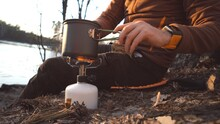 Theme Tourism Hiking And Traveling In Nature. Hands Caucasian Man Uses Equipping To Cook Food Outside. Tourist Places Pot Of Water On Burner Cylinder Cartridge With Gas For Boiling Water And Cooking