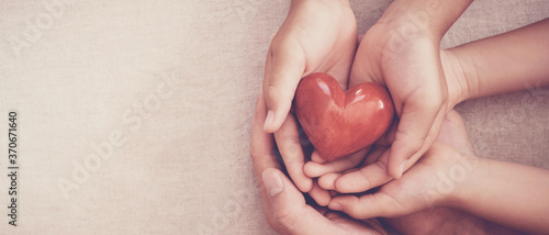 Fototapeta hands holding red heart, heart health, charity volunteer donation, CSR responsibility, world heart day, world health day, family day, adoption foster care home, all lives matter, no to racism concept obraz