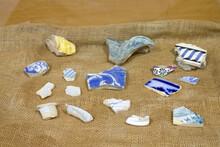 Pieces Of Broken Blue Porcelain On A Fabric In Rio De Janeiro.