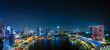 Wide panorama image of Marina Bay area in Singapore at night.