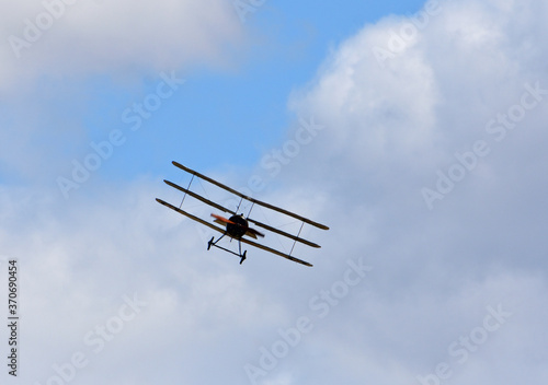 Canvas-taulu Vintage Sopwith Triplane in flight with clouds and blue sky.