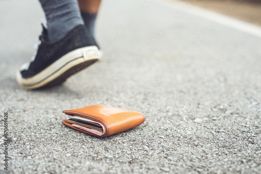 Fototapeta Man lose brown wallet on the road in tourist attraction. Losing wallet concept. Focus on wallet