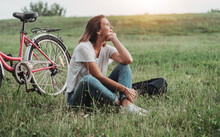 Beautiful Smiling Mature Woman Sitting Next To Bike On The Grass On A Green Field. Summer Country Vacation Adventure Concept