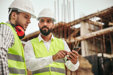 Technicians With Smartphone Working On Construction Site
