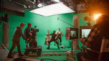 On Big Film Studio Professional Crew Shooting Period Costume Drama Movie. On Set: Directing Green Screen Scene With Gentleman Protecting Lady From Actor Playing Monster Wearing Motion Capture Suit